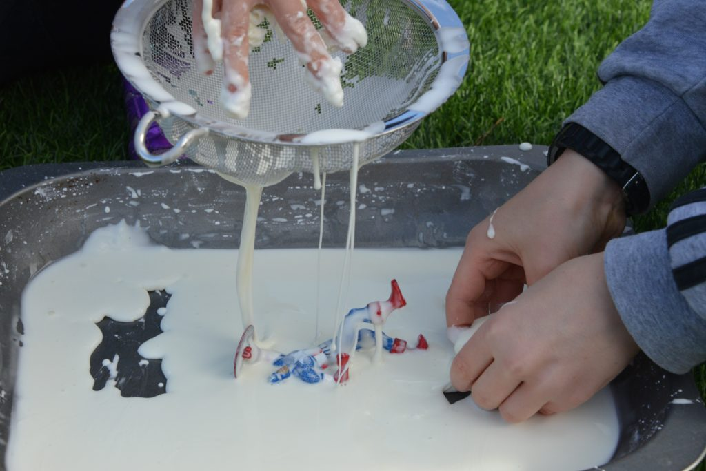 Child pouring cornflour gloop through a colander