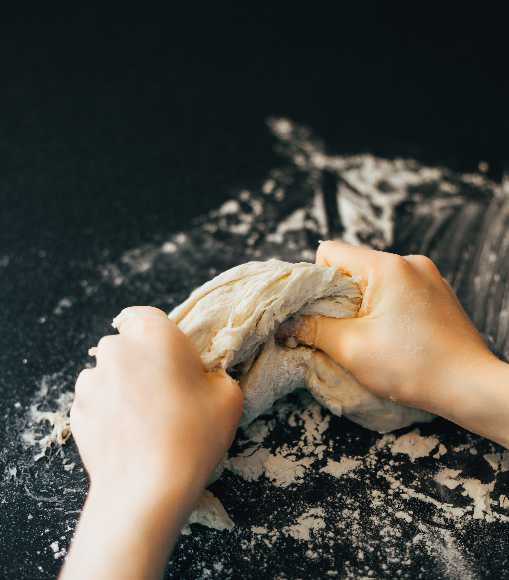 Pizza dough being kneaded by a child's hands