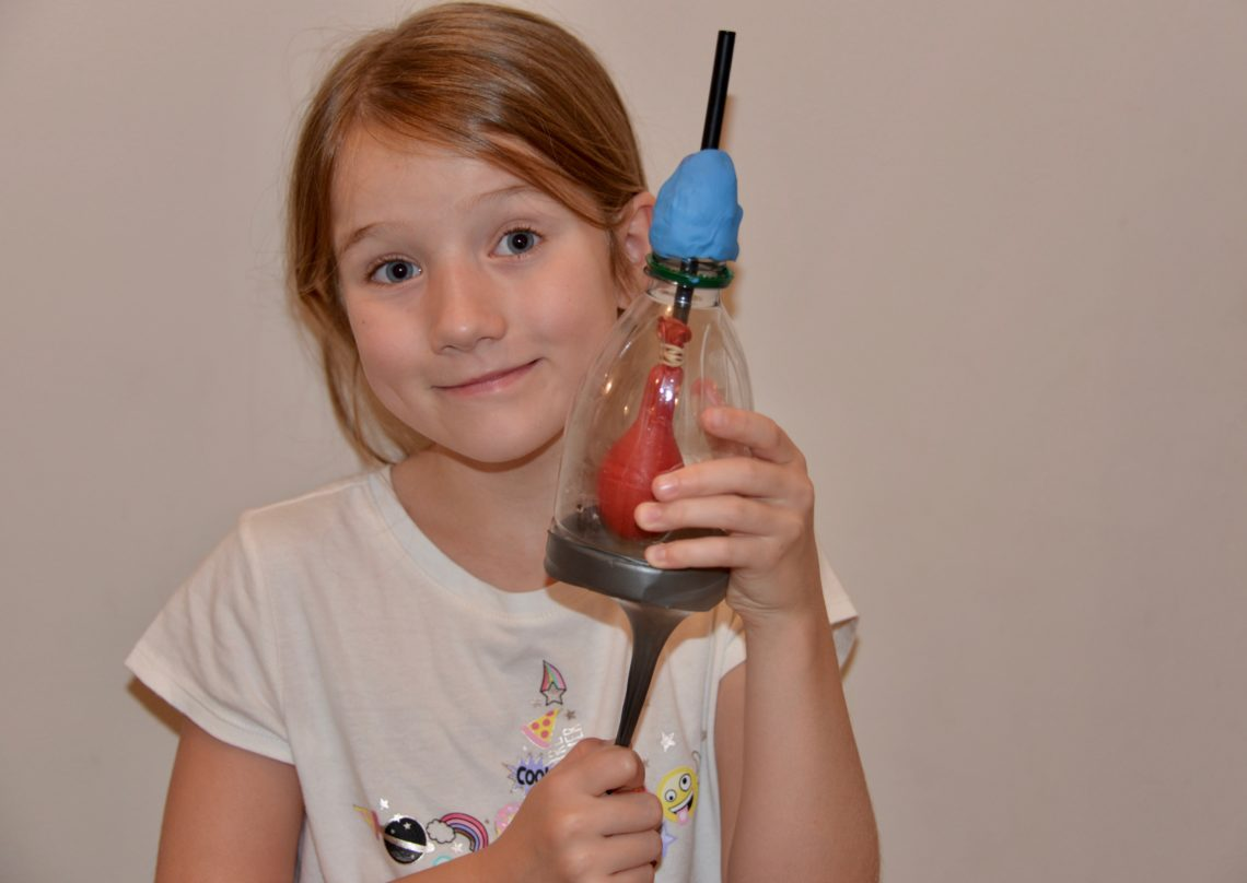 Child holding a model of a lung made with a plastic bottle and balloons