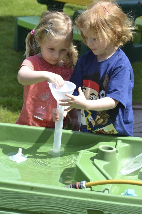 Children playing at a water table - science or kids