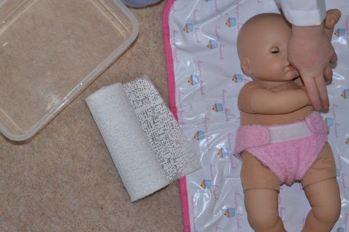 a doll at next to a roll of modroc - ready to have a plaster cast applied