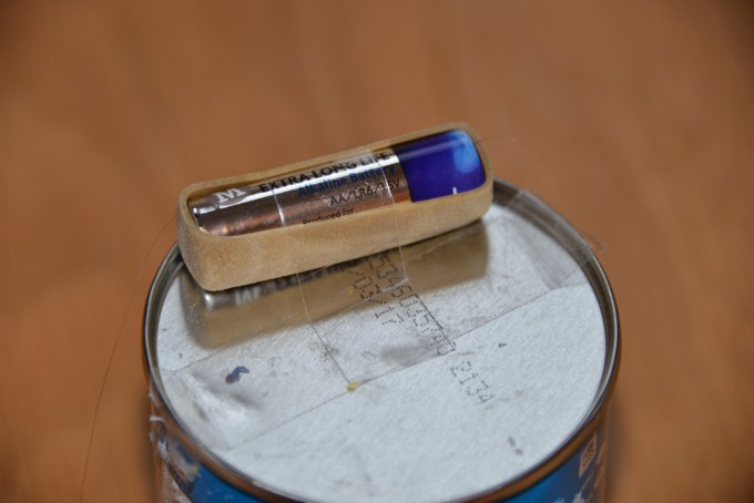 Battery for an art bot - step one - Pringles tube with a battery held in place with an elastic band #artbot