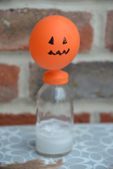 Balloon decorated to look like a pumpkin blown up on a jar - great experiment for Halloween