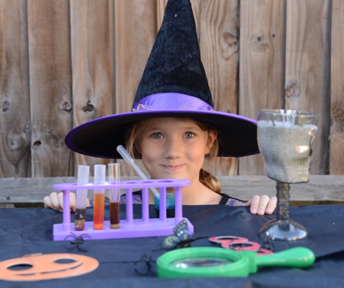 Little girl with a witches hat on sat behind a table of spooky potions