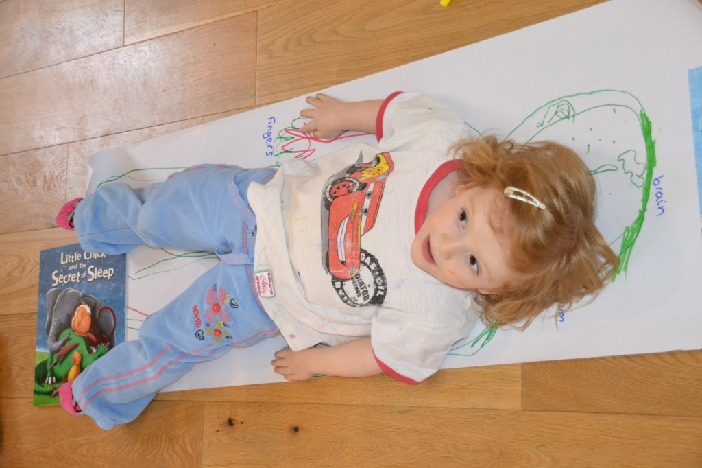 Young girl lying on a long piece of paper ready to be drawn around as part of a science activity