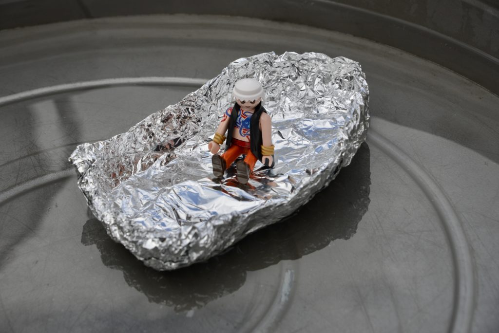 Image of a boat made from aluminium foil with a playmobil person inside