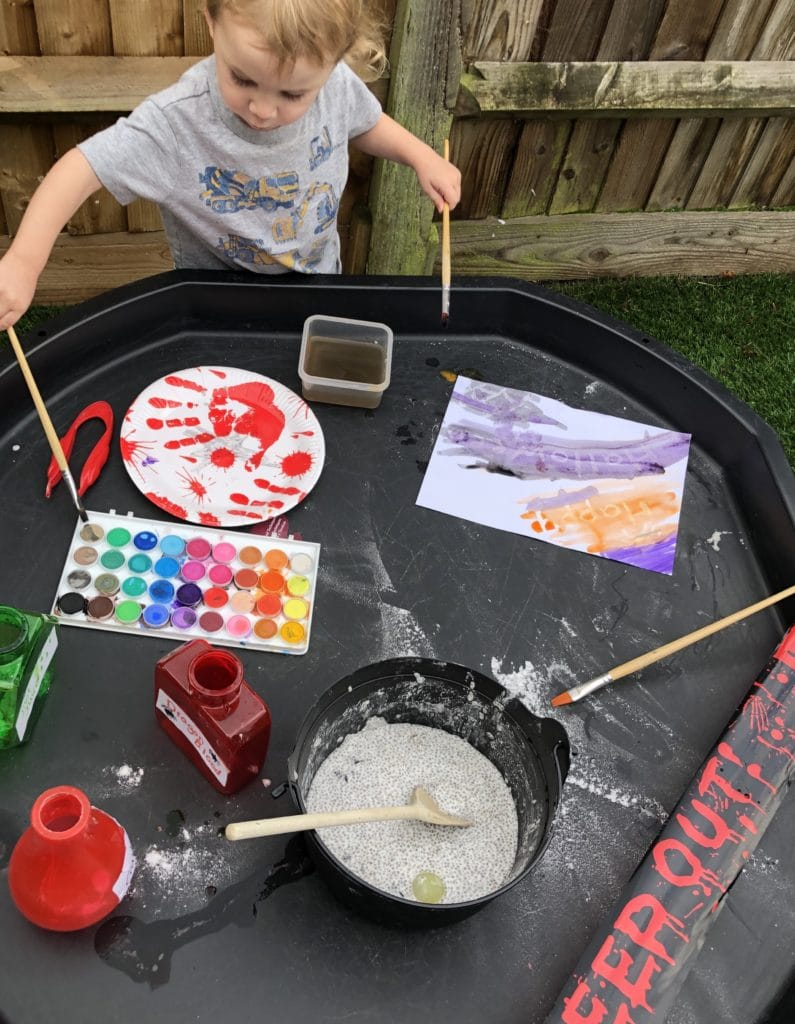 small boy stood next to a tuff tray with Halloween activities set up. Chia seed slime, crayon resist paintings and