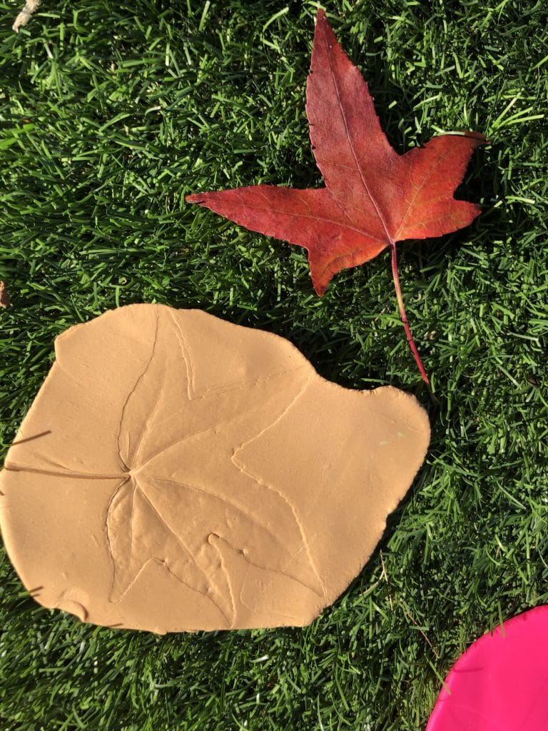 Orange play dough with a leaf imprint