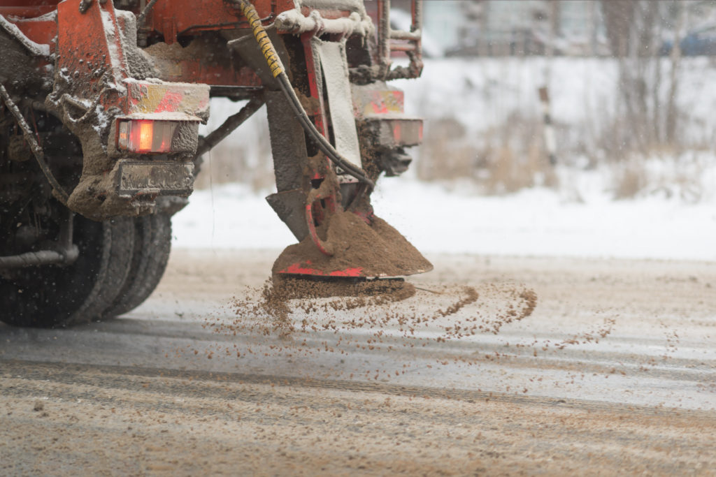 Image of a grit truck dropping grit on a road
