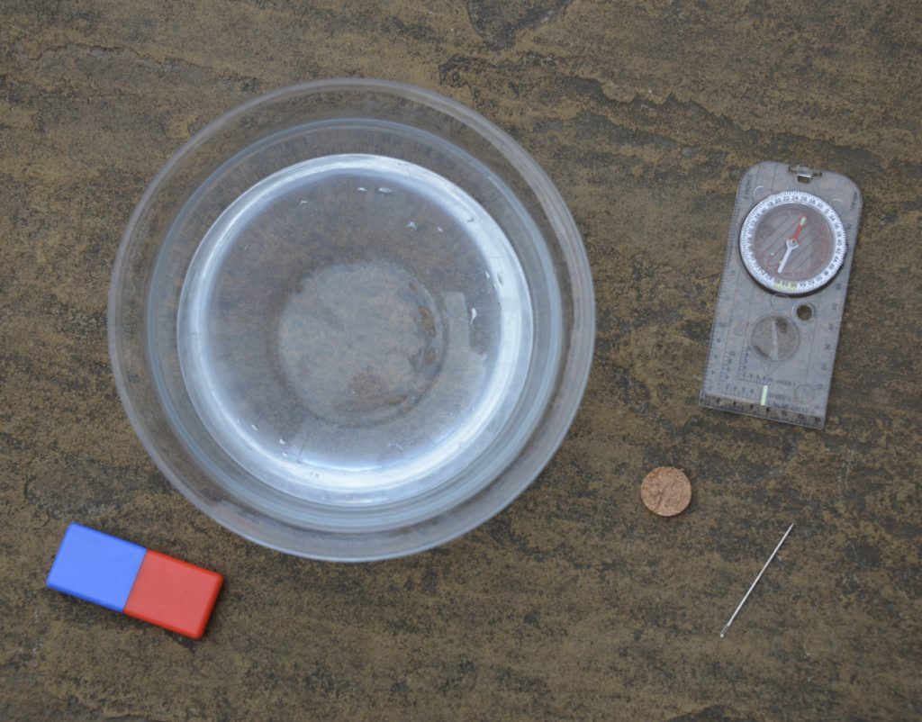 Bowl of water, compass, needle, slice of cork and a magnet ready to make a compass using a magnet