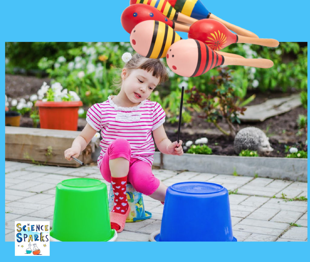 Image shows a young girl banging bucket drums