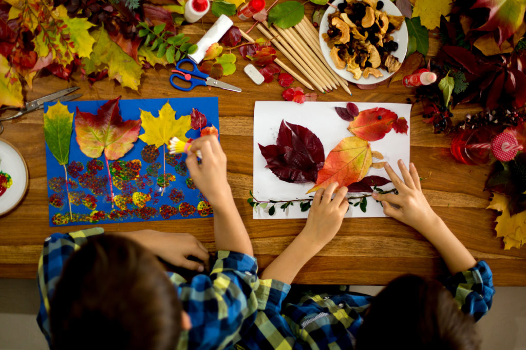 Children creating beautiful autumn collages from natural materials