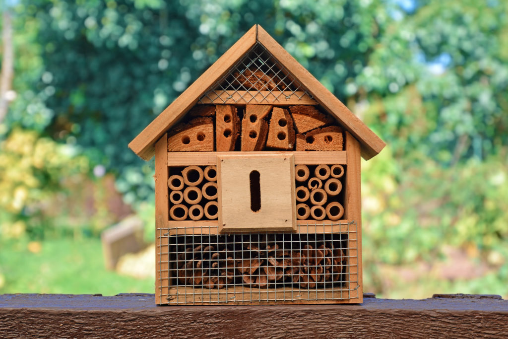 A bee hotel made from wood, tubes and other materials.