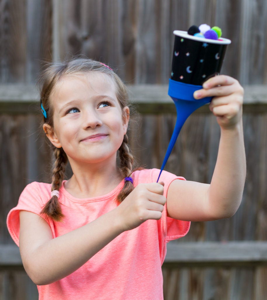 Girl holding a DIY seed dispersal machine for learning about exploding seeds