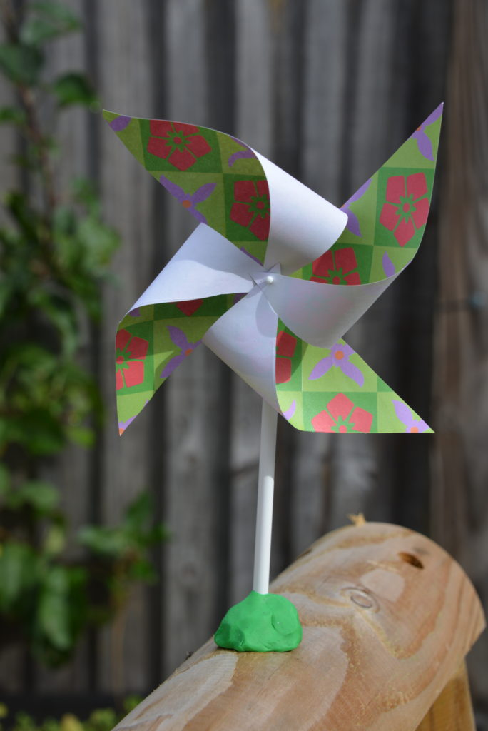 DIY pinwheel made with paper, a pin, pencil and plasticine. Pinwheel is sat outside on a wooden plank.