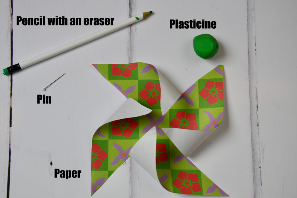 Image shows paper cut ready to make a pinwheel, a blob of plasticine, pencil with an eraser on the top and a pin