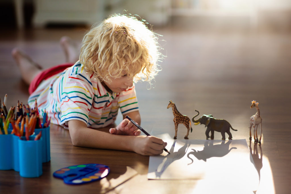child drawing around plastic toy animals
