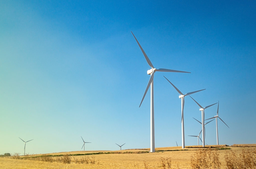Image of a wind farm showing wind turbines in a row