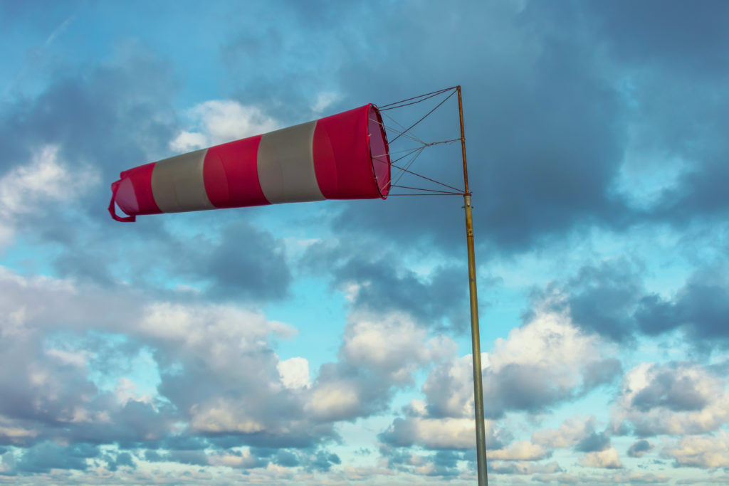 Image of a red and white windsock on a cloudy day