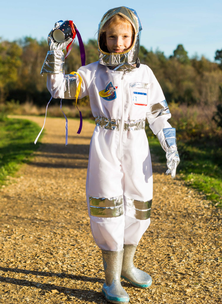 Image of a girl holding a homemade wind sock dressed as an astronaut
