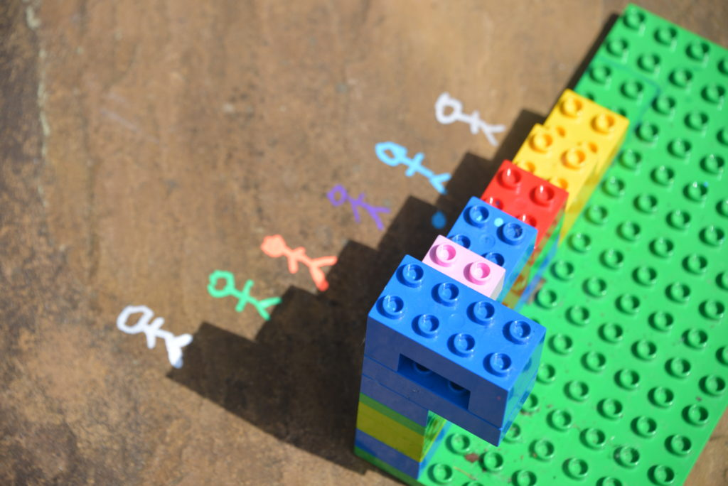 Image of a shadow made with duplo and drawings on the ground to make a picture using the shadow. Image shows a shadow of steps with stick people drawn on the floor stood on each step.