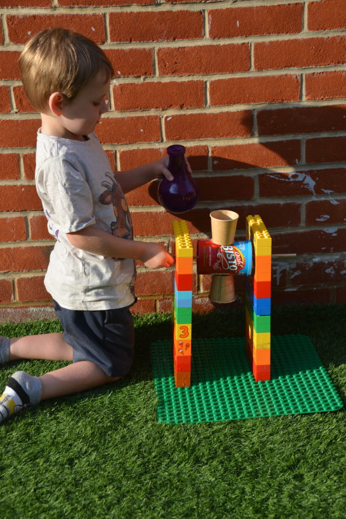 child testing a DIY water wheel